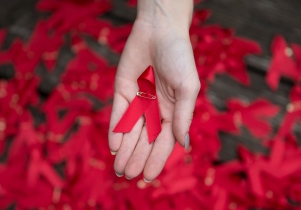 Red ribbon supporting World Aids Day in a hand