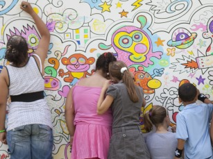 children in a group drawing on wall