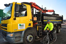 Councillor Bassam Mahfouz sitting on a bicycle next to a lorry fitted with the new safety technology