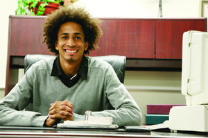 Young black man sits at a desk in an office.