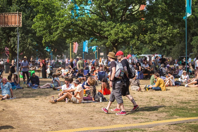 Crowds at a summer music festival in a park