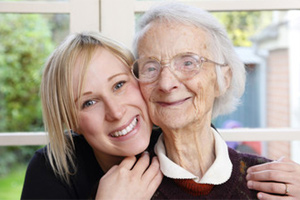 younger woman hugs an older  elderly women